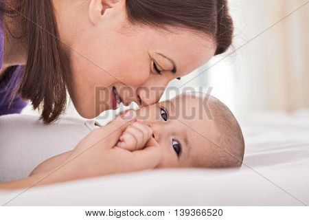 Young Mother Cuddling Her Gentle Baby