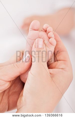 Baby foot massage soft skin, close up