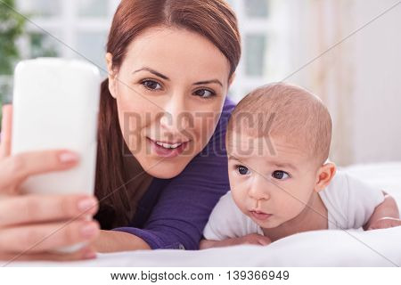 Young Mother With Son Looking To The Mobile Phone