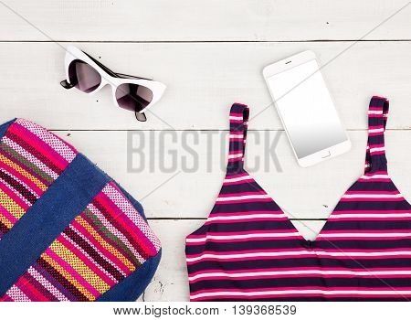 Colorful Striped Bag, Swimsuit, Smart Phone And Sunglasses On White Wooden Desk