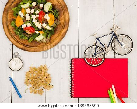 Bicycle Model, Salad Of Fresh Vegetables, Red Notepad, Stopwatch And Currants On A White Wooden Tabl