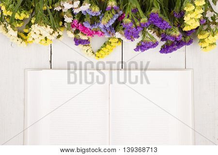 Beautiful Colorful Flowers And Open Blank Book On A White Wooden