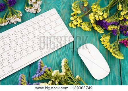 Wireless Slim Keyboard, Mouse And Colorful Flowers On Blue Wooden Table