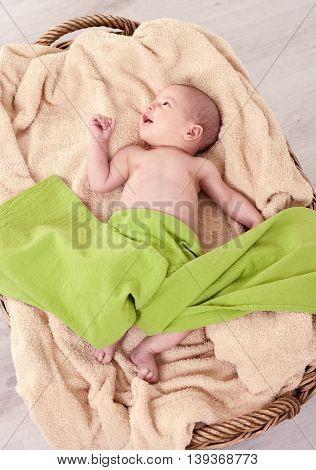 Smiling beautiful newborn baby on green blanket