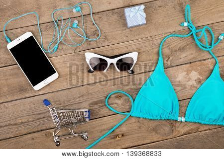 Blue Swimsuit, Smart Phone, Sunglasses, Headphones, Gift Box And Shopping Carts On Brown Wooden Tabl