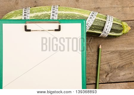 Marrow Squash, Measure Tape And Blank Clipboard On Brown Wooden Table