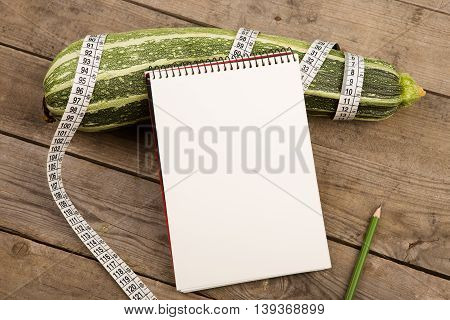 Marrow Squash, Measure Tape And Blank Notepad On Brown Wooden Table