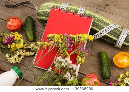 Marrow Squash, Measure Tape, Blank Red Notepad, Bottle Of Water, Flowers, Tomatoes And Cucumbers On