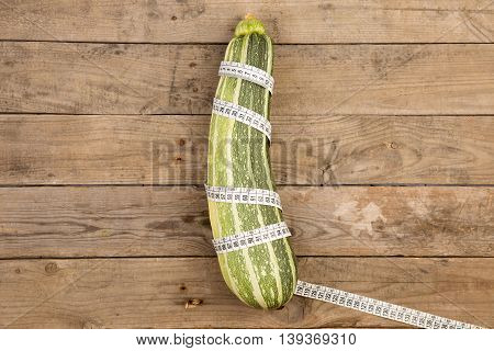 Marrow Squash And Measure Tape On Brown Wooden Table