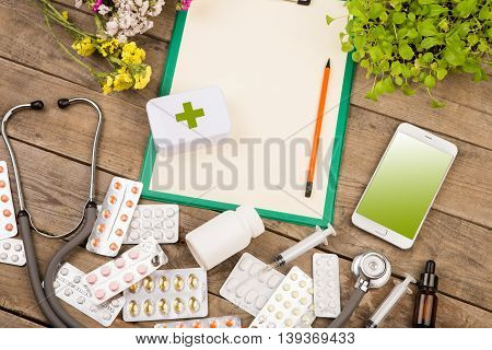 Pills, Syringe, Stethoscope, Clipboard, Smart Phone On Brown Wooden Desk