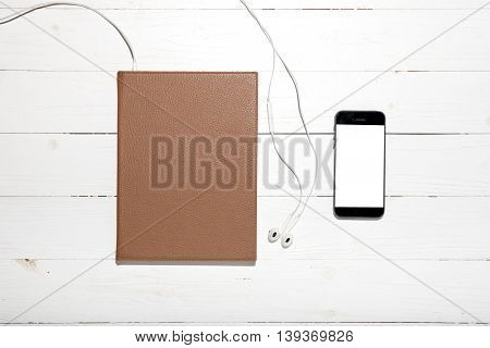 top view of earphone with notebook and phone