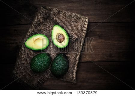 Halved avocado on a rustic table. Top view avocados image with vintage effect