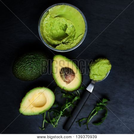 Halved avocado spread pasta. Top view avocados with Traditional Mexican sauce Guacamole on dark table