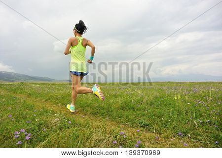 healthy lifestyle young woman runner running on beautiful trail in grassland