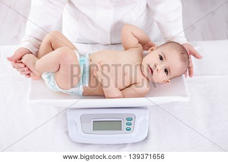 Female Pediatrician Weighing Baby In Office