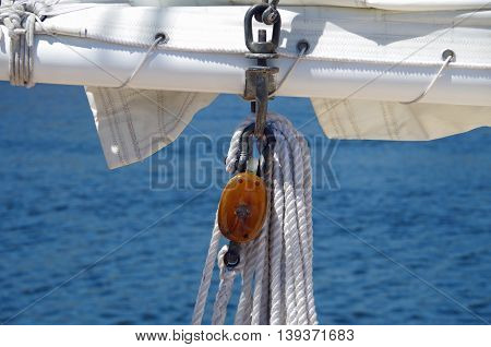 White sail and wood rigging of sailboat with water background