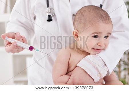 Baby receiving vaccine in lab, close up