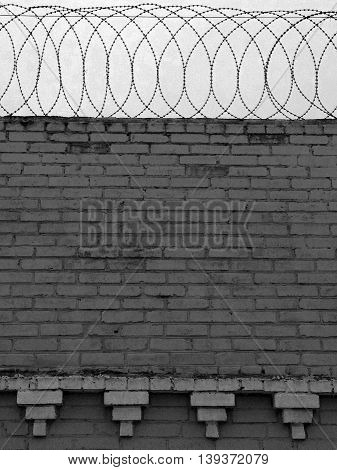 Black and white image of brick wall with barbed wire on top