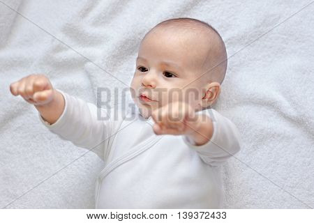 Strong baby looking at fists,portrait close up