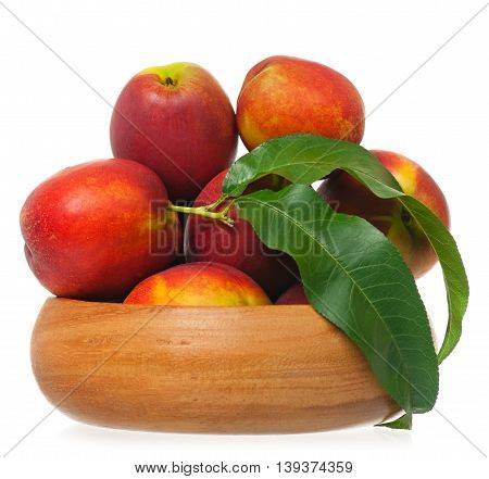 Fresh tasty nectarines in a bamboo dish isolated on white background