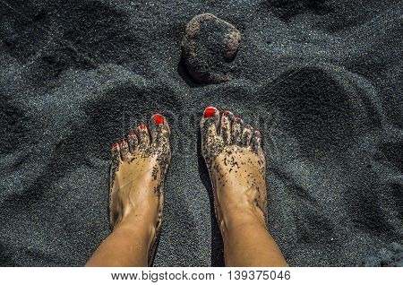 Female bare feet with red nails on black sand beach in Tenerife