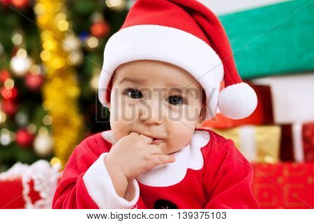 Cute Baby Santa Claus With Fingers In Mouth