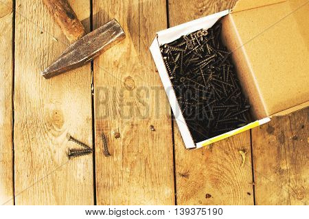 box with screws and tools on a wooden background
