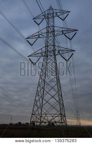 High voltage pylon seen from below on a cloudy sky background
