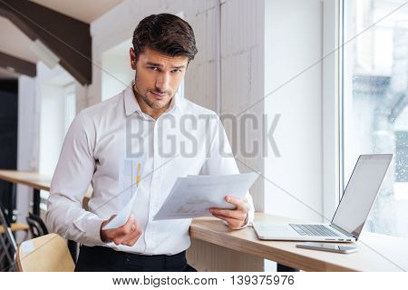 Handsome young businessman working with documents and laptop in office looking at camera