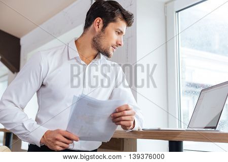Handsome young smart businessman working with documents in office