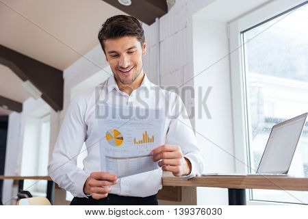 Handsome young smiling businessman working with documents in office