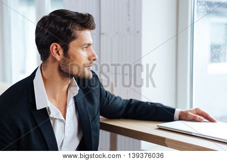 Handsome pensive young business man sitting and looking at the window in cafe