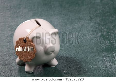 white color piggy bank with tag- education