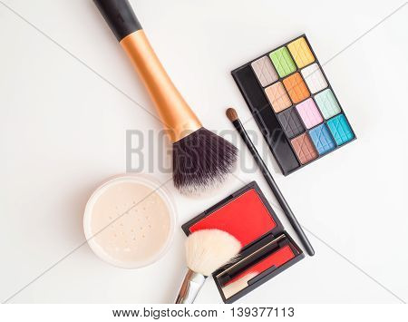 Top view of cosmetic makeup items - makeup brush eyeshadow palette brush on powder - on white background