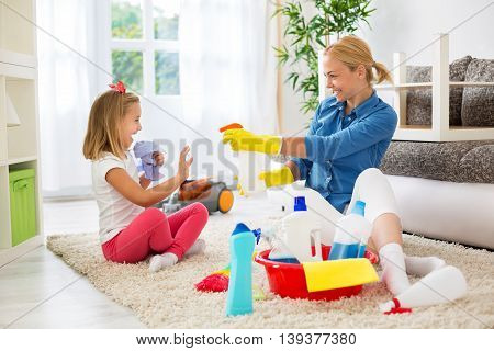 Mother And Little Girl Cleaning House And Playing
