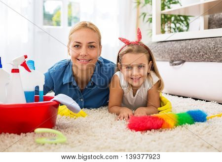 Woman And Cute Girl Lying On Floor With Cleaning Tool