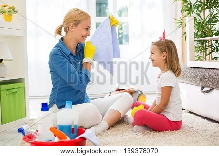 Mother and kid cleaning room together, family teamwork