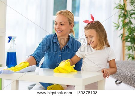 Worth families cleaning table with mop at home