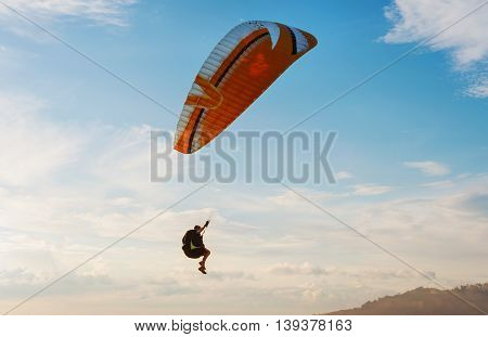 Man with glider on the sky blue sky and white cloud in evening light