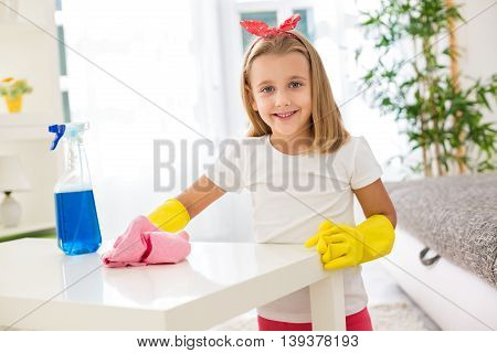 Adorable Worth Girl Holding Pom And Cleaning A Table At Living Room