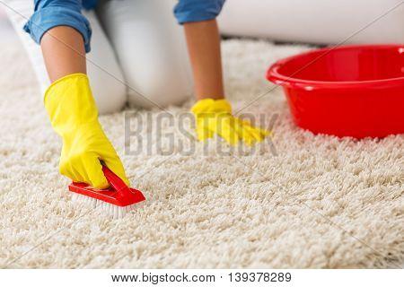 Woman Washing Carpet With Brush