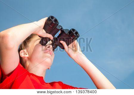 Low angle view of teen boy wearing red tshirt looking through binoculars against blue summer sky