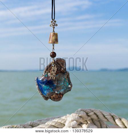 Hand made necklace on the Balaton lake background
