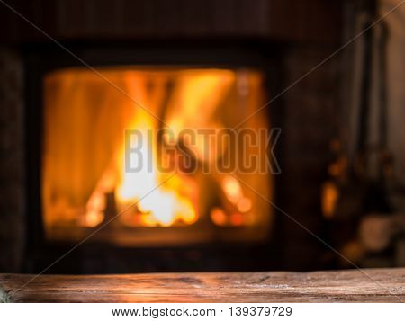 Old wooden table and fireplace with warm fire on the background.