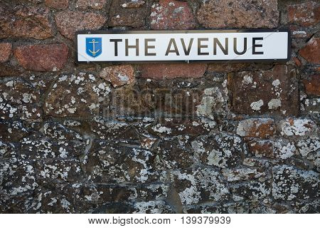 Color image of a street name placard on a wall.