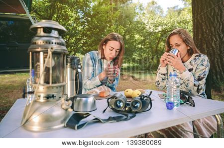 Young women drinking cups of hot coffee in the breakfast in a cold morning into the forest