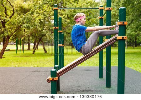 young beautiful girl swings the press in the gym outdoor sport place