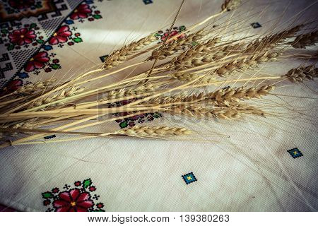 Ears of barley on a white tablecloth with embroidery in ethnic style. Photos in a grunge style.