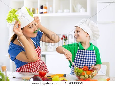 Mother And Child Having Fun In Kitchen Playing With Vegetables And Prepare Lunch