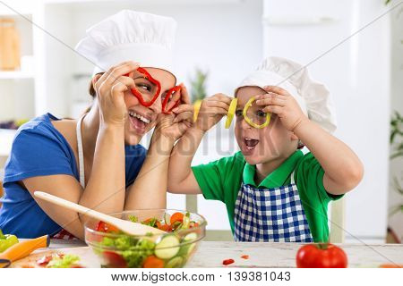 Happy Family Playing With Vegetables In Kitchen